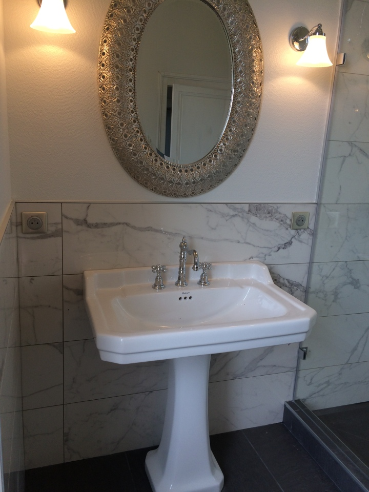 Mixing styles, classic fixtures, marble walls.
